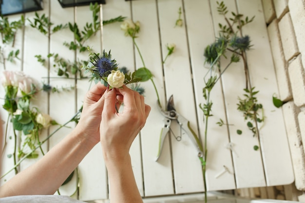 Woman florist hands collects flowers for groom boutonniere