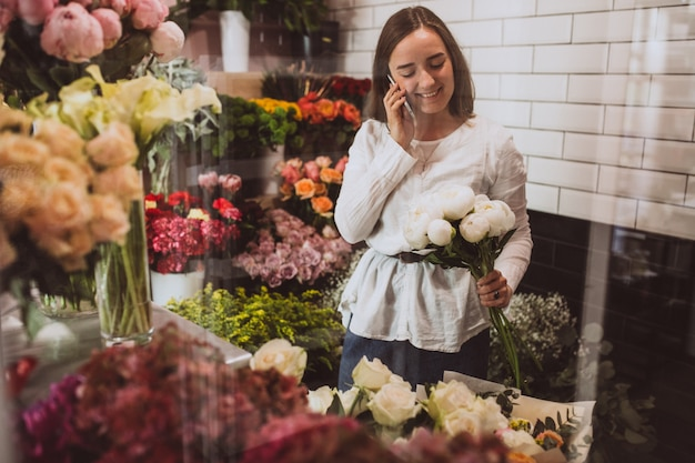 Woman florist at her own floral shop taking care of flowers