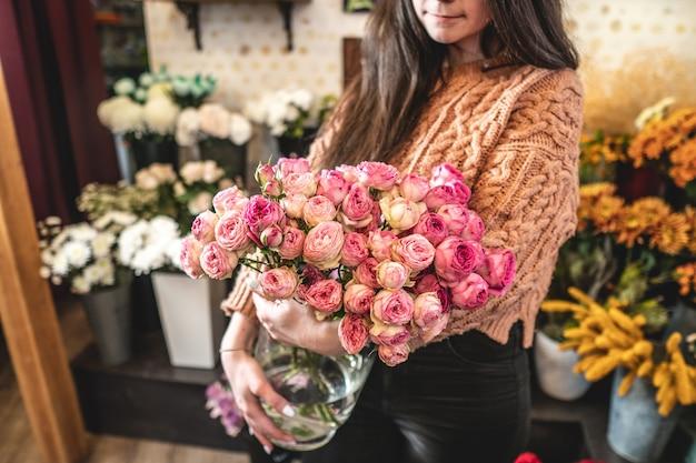 女性の花屋は、フラワーショップで咲くピンクのバラの大きな美しい花束を持っています