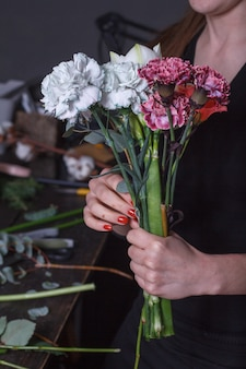 Woman florist makes a bouquet