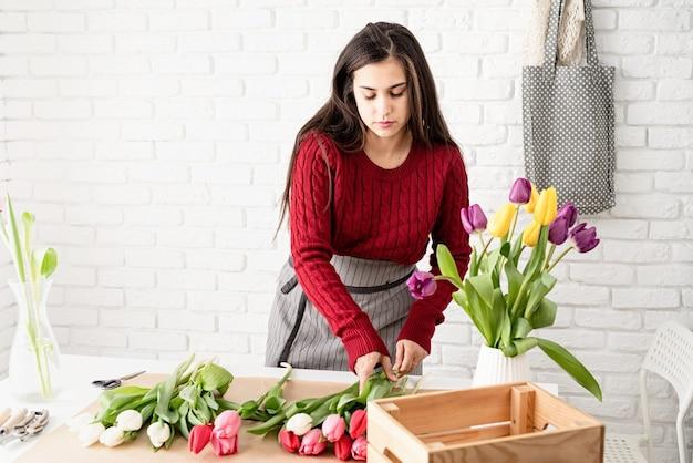 신선한 다채로운 튤립 꽃다발을 만드는 여자 꽃집