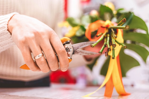 Woman florist pruning rose on bouquet in flowers shop