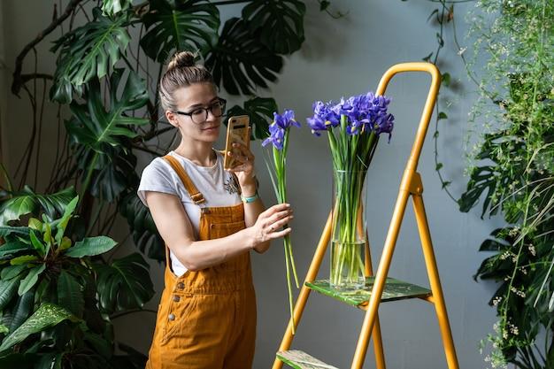 Женщина-флорист фотографирует букет фиолетовых ирисов в вазе
