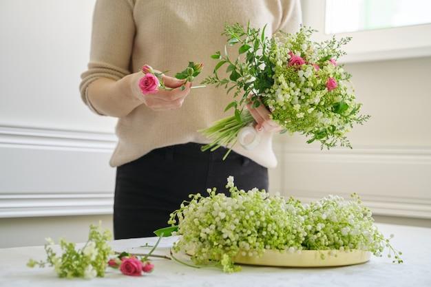 花束を作るテーブルの上にさまざまな花を持つ女性の花屋y
