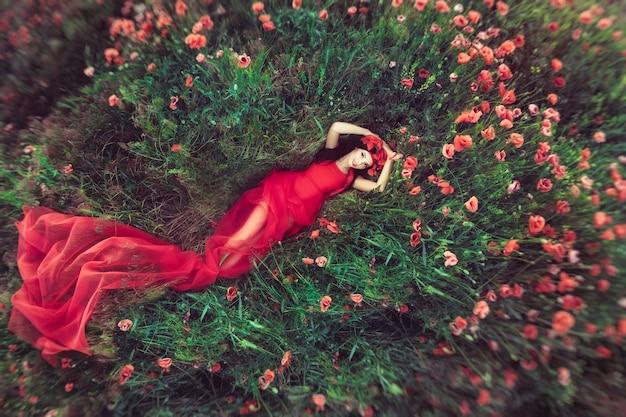 Woman in flower poppy field in summer