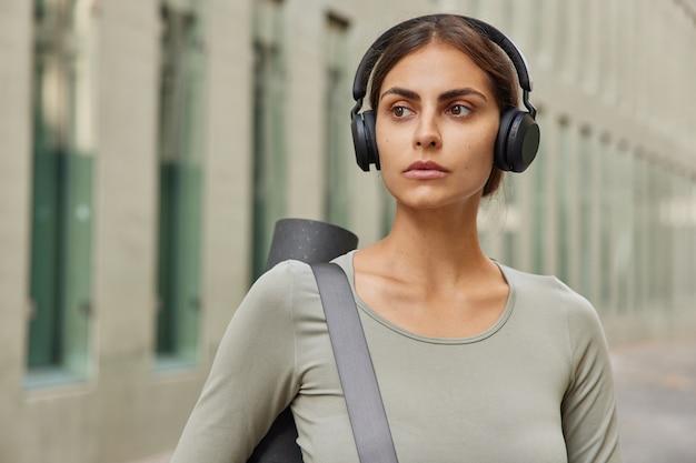 距離に焦点を当てた女性はスポーツ服を着て肩に丸めたマットを運び、屋外でトレーニングポーズを取りますワイヤレスヘッドホンで音楽を聴きますスポーツをします