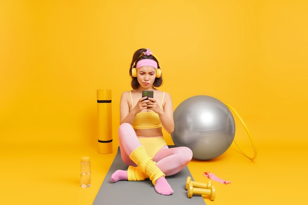Woman focused at smartphone display uses sport equipment dressed in sportsclothes
