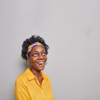 Woman focused above smiles broadly has happy mood reads promo text onhead wears headband and yellow shirt poses on grey