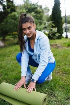 공원에서 운동 후 롤 피트니스 또는 요가 매트를 접는 여자.