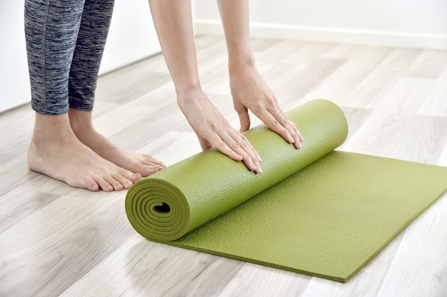 Woman folding yoga or fitness mat after working out at home, home exercise workout.