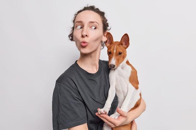 女性は唇を折りたたむ素敵なバセンジー犬は彼女の愛らしいペットが白で隔離された黒いtシャツを着た手に家畜を運ぶのを楽しんでいます