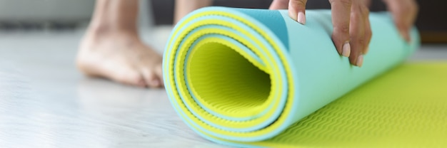 여자는 거실에서 집에서 운동한 후 요가나 피트니스 매트를 접습니다