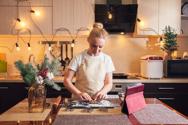 디지털 태블릿에서 조리법을 따르는 여성은 부엌에서 크리스마스 진저브레드 쿠키를 요리하기 위해 곰팡이로 반죽을 잘라냅니다.