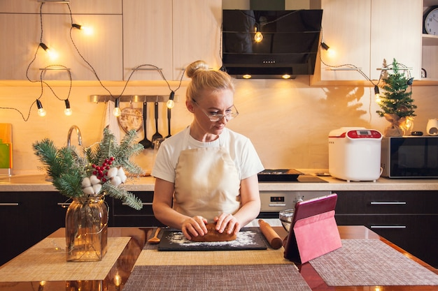 디지털 태블릿에서 조리법을 따르고 부엌에서 크리스마스 진저브레드 쿠키를 요리하기 위해 반죽을 반죽하는 여자.