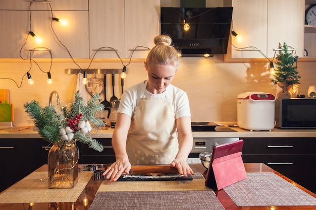 여자는 디지털 태블릿에서 조리법을 따르고 부엌에서 크리스마스 진저브레드 쿠키를 요리하기 위해 롤링 핀으로 반죽을 굴립니다.