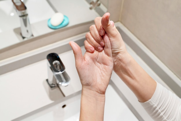 Woman following steps to wash properly with soap and sanitize and disinfect hands. cleaning measures against propagation of viral covid 19 disease. coronavirus, health and hygienic concept.
