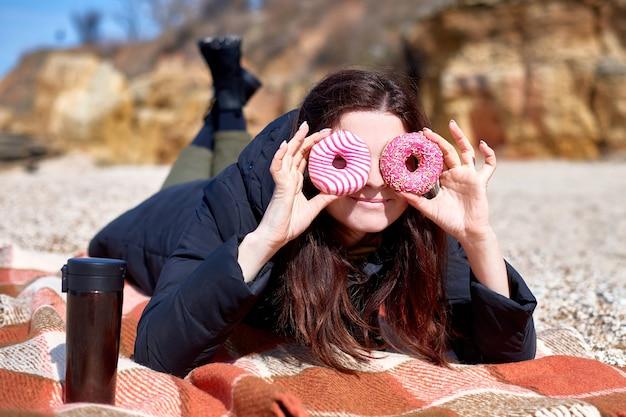 湖や海岸に格子縞の毛布を横になっている手にドーナツを持って浮気している女性