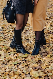 Woman foot among yellow leafs at autumn colorful park