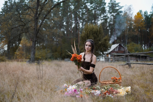 Woman in the forest collects an autumn bouquet next to a basket and a house on the background