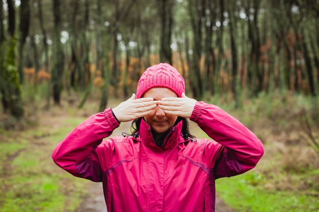 Woman in the forest covering her eyes