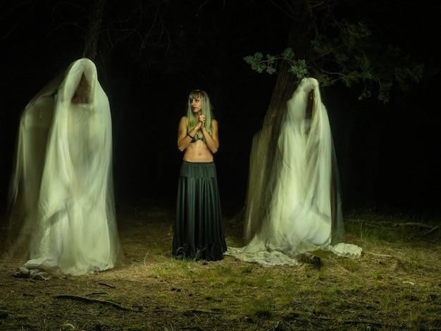 Woman in the forest between two ghosts watching her