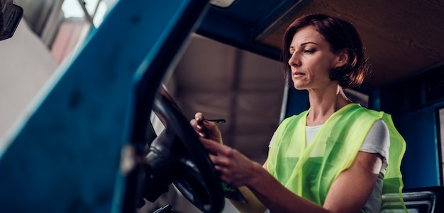 Woman forklift operator signing document in the vehicle
