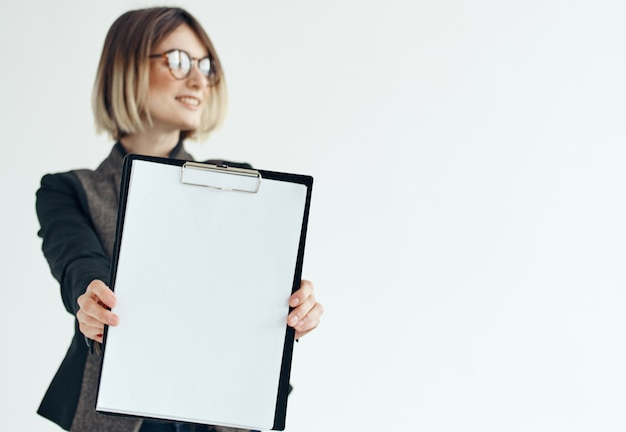 A woman in a formal suit holds a white sheet of paper