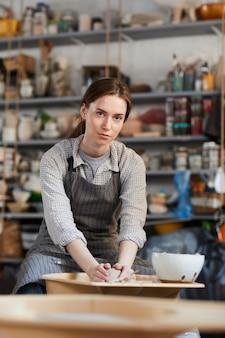 陶器のホイールに花瓶を形成する女性