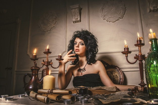 Woman fortune-teller guesses fate of night at table with candles. halloween magic tale, mysticism, girl calls spirits. black magic