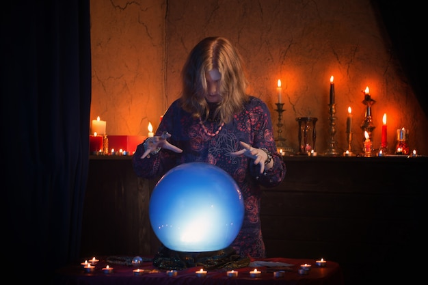 Woman fortune teller with illuminated crystal ball