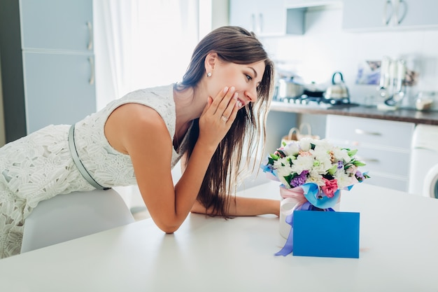 Woman found bouquet of flowers in gift box and envelope with card on kitchen.