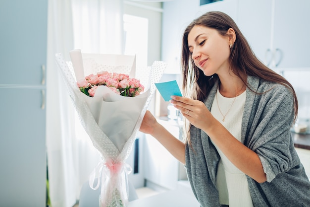 Woman found bouquet of flowers on kitchen and reading card on kitchen. surprise. present for holiday