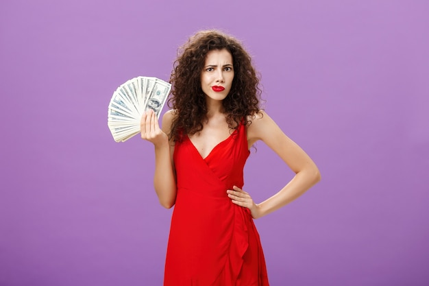 Woman found husband stash being questioned and confused. intense thoughtful charming and elegant wife with curly hairstyle in red dress holding lots of money waving cash over purple background.