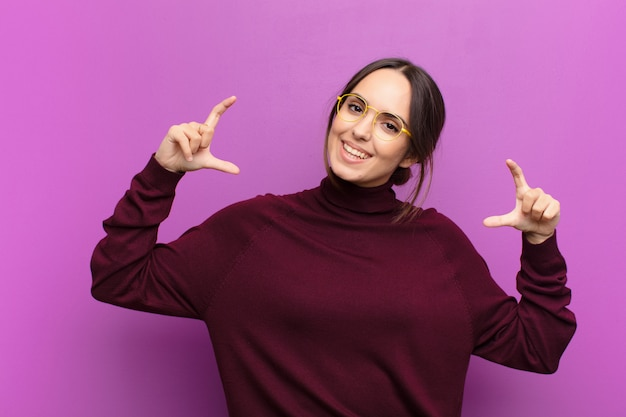 Woman framing or outlining own smile with both hands, looking positive and happy, wellness concept