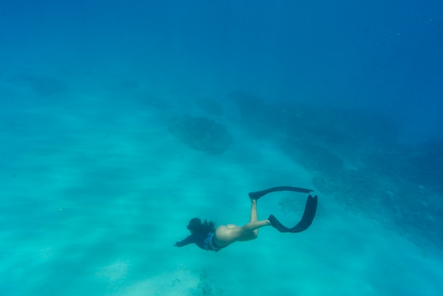 Woman freediving with flippers underwater