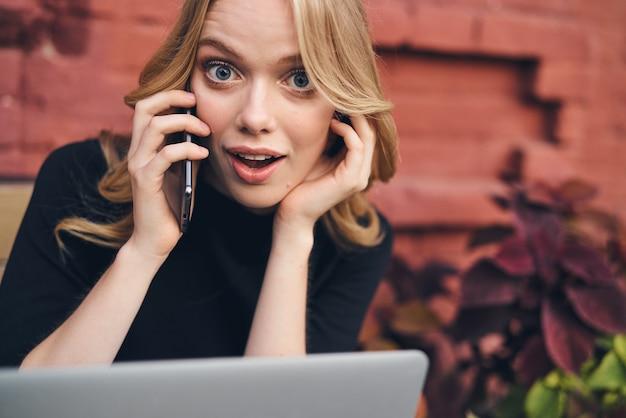 ノートパソコンの前で電話で話している屋外の女性フリーランス