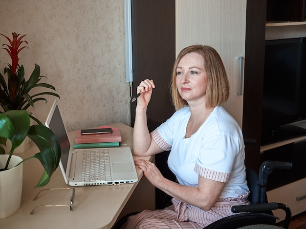 A woman freelancer, disabled in a wheelchair, works remotely from home on a laptop, holding a pen in her hand