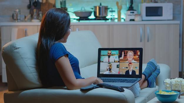 居間のソファーに座ってウェブチャット会議をしている女性フリーランサー。オンライン会議で話し合っているリモートワーカー、ラップトップの前で作業しているビデオ通話とwebカメラを使用して同僚と相談している