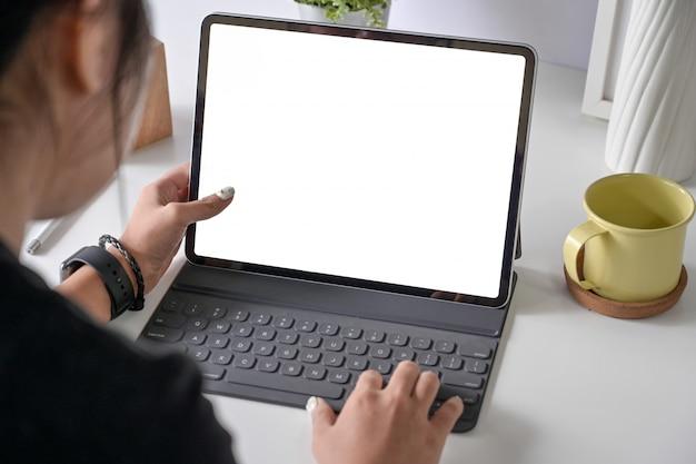 여자 프리랜서는 광고 그래픽 디스플레이를위한 빈 복사본 공간 스크린 태블릿 컴퓨터에서 작업하고 있습니다