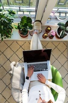 여성 프리랜서는 집에서 노트북 작업을 하는 안락의자에 앉아 식물이 있는 창턱에 발을 올려 놓습니다.