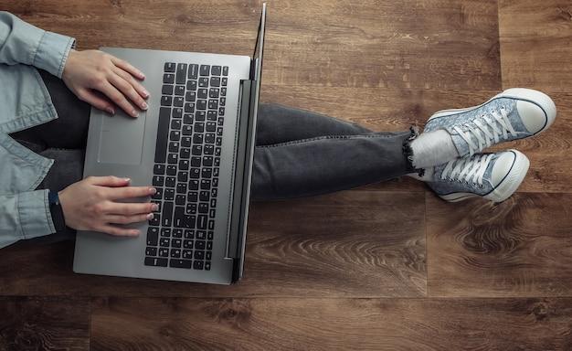 나무 바닥에 앉아서 노트북에 입력하는 여자 프리랜서.