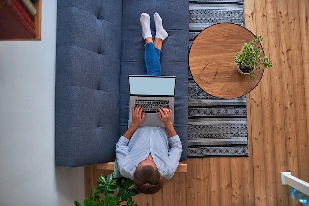 Женщина-фрилансер сидит на диване и работает онлайн на компьютере в удобном домашнем рабочем месте с комнатными растениями. вид сверху