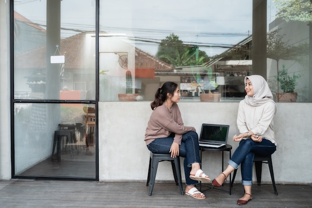Woman freelancer with friend sitting in cafe