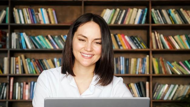 짧은 머리를 가진 여성 프리랜서는 회색 노트북 근처의 온라인 취업 면접에서 지역 도서관 폐쇄의 대형 책장에 대고 고개를 끄덕입니다.