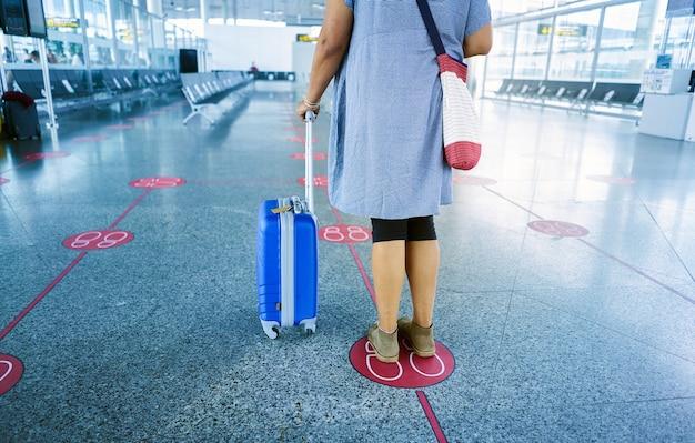 コビッドを避けるために社会的距離を維持している空港で待っているスーツケースを持った後ろからの女性