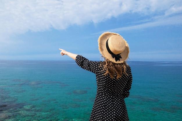 하늘에 대 한 밀 짚 모자에 뒤에서 여자
