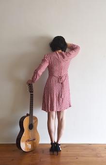 Женщина сзади с гитарой на стене