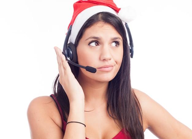 白い壁に分離された笑顔で話している赤いサンタの帽子をかぶってテレマーケティングコールセンターからの女性
