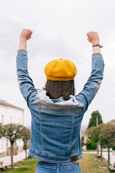 Woman from behind with hands up and lgbt bracelet, vertical photo