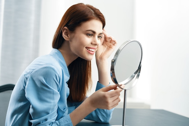 Woman in front of the mirror cosmetics home care